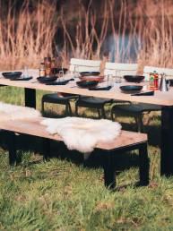 Luxe tuinmeubelen. Lange tuintafel eiken hout en zwart staal. Met Weltevree schapenvacht wit.